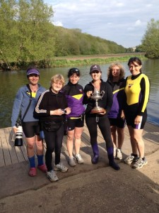 Six ladies stood by a river bank holding a trophy